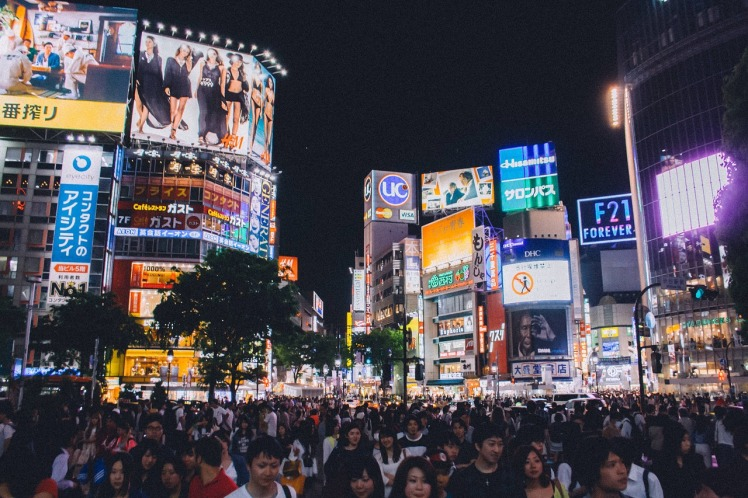 Shibuya crossing at night, one of the busiest intersections in Tokyo, lined by tall buildings with large billboard advertisements and bright neon lights.