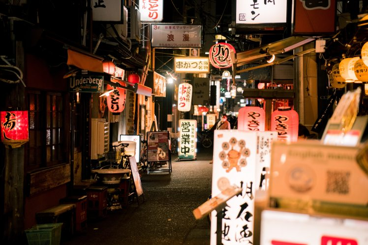 Traditional Japanese paper lanterns light up a small lane full of shops in Tokyo.